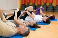 vign1_7889467-happy-fitness-people-class-in-a-row-doing-some-aerobic-stretching-after-workout-at-gym